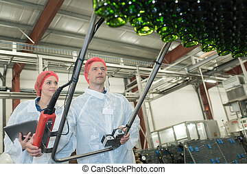 two employees in coats standing in wine manufactory