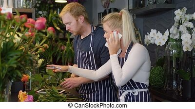 Two employees in shop - Side view of young blonde in apron...