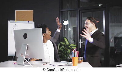 two employees raising hands when successfully closing big business deal