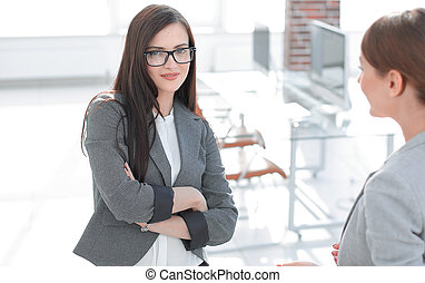 two employees talking standing in the office