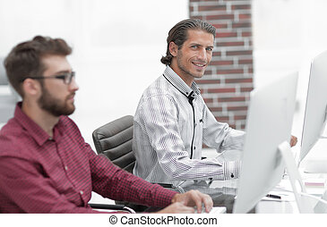 two employees work in the office