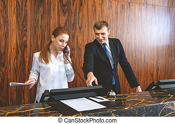 Two employees working at reception