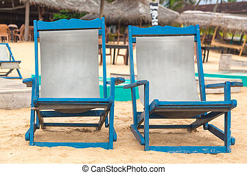 Two empty blue deckchairs at sandy beach.