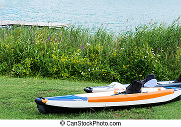Two empty canoes stand on the lawn by the lake.