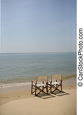Two empty chairs on a beach