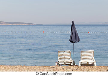 Two empty deck chair and a blue parasol