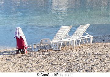 Two empty deck chair and a carrier