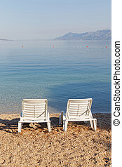 Two empty deck chair on the beach