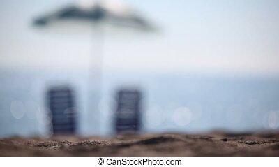 Two empty deckchairs stand on beach under parasol