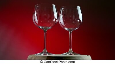 Two empty glasses for wine on a red background rotates on wooden platform