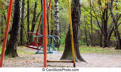 Two empty metallic swing sway on grove at autumn day