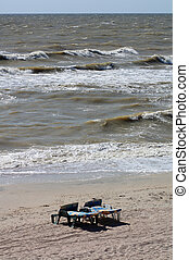 Two empty plastic deck chairs on the background of sea waves on a summer afternoon
