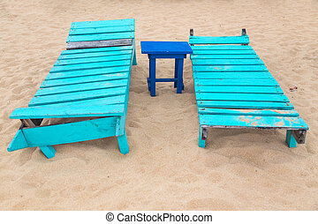 Two empty turquoise sunbeds at sandy beach.