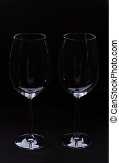 Two empty wine glass on black background.