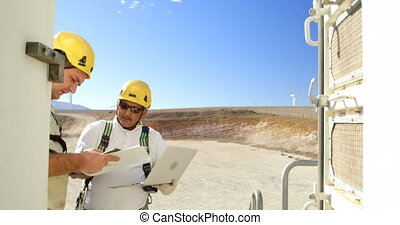 Two engineer discussing over laptop in the wind farm 4k -...