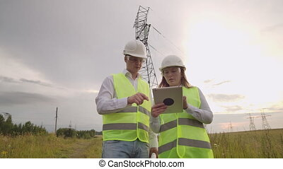 Two engineers, a man and a woman in helmets with a tablet of...