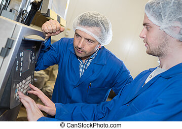 two engineers check functionality of industrial machine