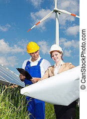 Two engineers look at construction plan of solar panels