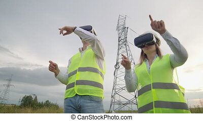 Two engineers of power engineers in VR glasses move their...