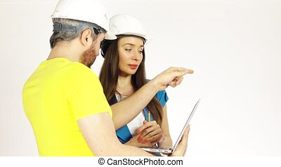 Two engineers or architects wearing had hats discuss project and use the laptop against light background. 4K clip