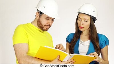Two engineers or architects wearing had hats discuss project and look through papers in a yellow folder. 4K clip