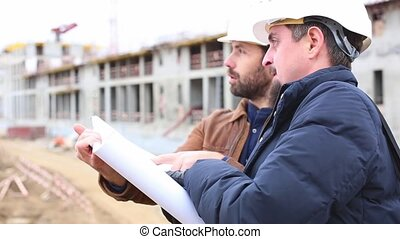 Two engineers talk about the project for the construction building. They look at both paper projects