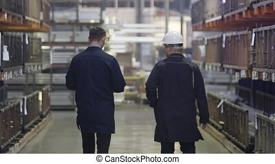 Two Engineers Walking Through Heavy Industry Manufacturing Factory Warehouse. Heavy metallurgical industrial products, manufacturing business production concept. Slow Motion.