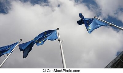 Two EU banners waving cheerily in a cloudy blue sky in...