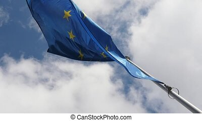 Two EU flags fluttering solemnly in a cloudy blue sky in...