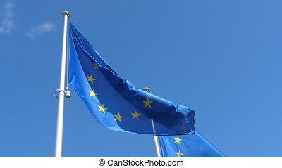 Two EU flags waving freely on flagpole in celeste sky in...