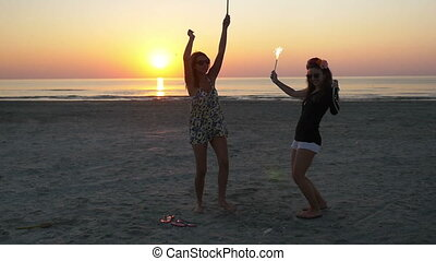 Two euphoric young women partying with firework candles on the beach at sunrise