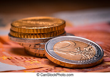 Two euro coins over euro banknotes. Currency of the European Union.