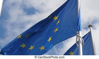 Two European Union flags with golden stars flying freely in...