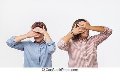 Two european women mother and daughter covering their faces using hands.