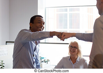 Two excited diverse male workers give fist bump celebrate teamwork