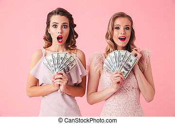 Two excited girls 20s in fancy outfit holding fan of money 100, isolated over pink background