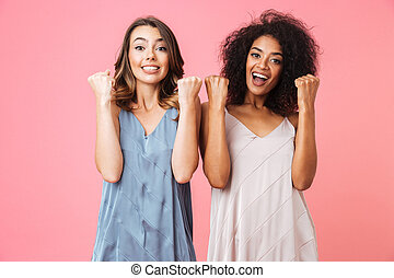 Two excited young girls dressed in summer clothes
