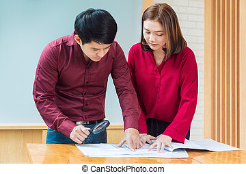 Two executive business man and woman looking at their architecture blueprint to plan their project