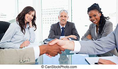 Two executives and their director smiling while looking at colleagues shaking hands