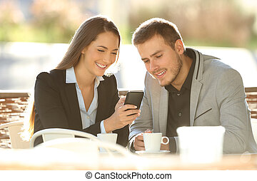 Two executives using a smart phone in a coffee shop