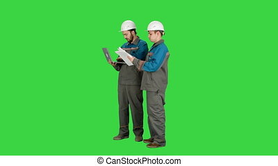 Two experienced industrial technicians work on laptop on a Green Screen, Chroma Key.