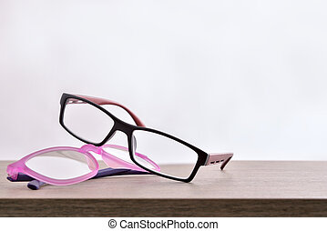 Two eyeglasses on wood table with white background