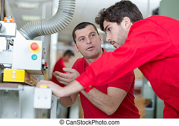 two factory engineer operating machine in drinks production plant