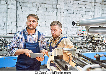 Two Factory Workers Operating Modern Machine
