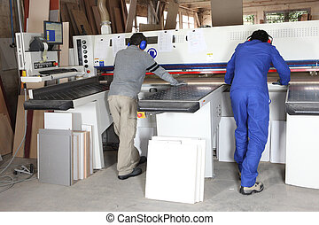 Two factory workers operating saw