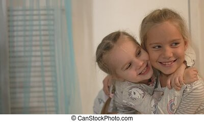 Two fair-haired little girls laugh and smile at home
