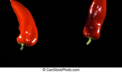 Two falling red peppers, slow motion - Two falling red...