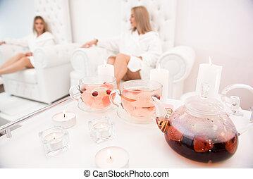 Two famale friends in spa have fun, talk drinking fruit tea.