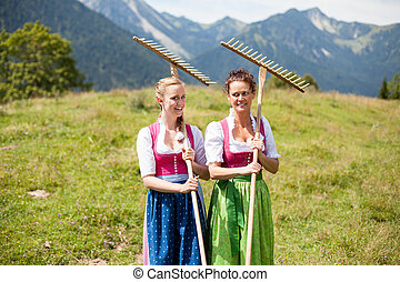 Two farmers in dirndl with rakes in an alpine meadow
