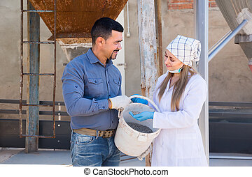 Mature farmer and woman in white coat holding bucket with pelleted food for hogs .